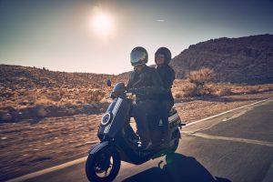 par kører på landevejene på Niu el scooter