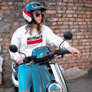 pige med Niu hjelm og solbriller sidder på niu el scooter